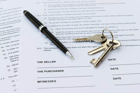 Real estate sales contract with keys and pen
