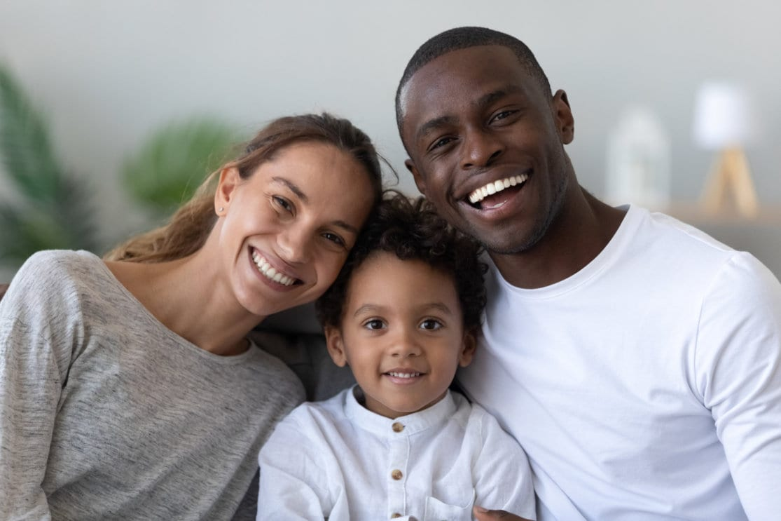 Portrait of happy multiracial family with little biracial son